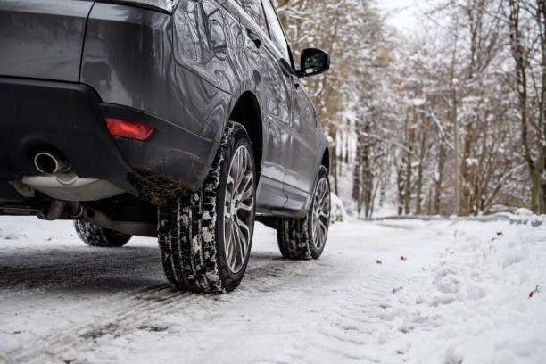 Voiture qui roule sur la neige avec des pneus hiver