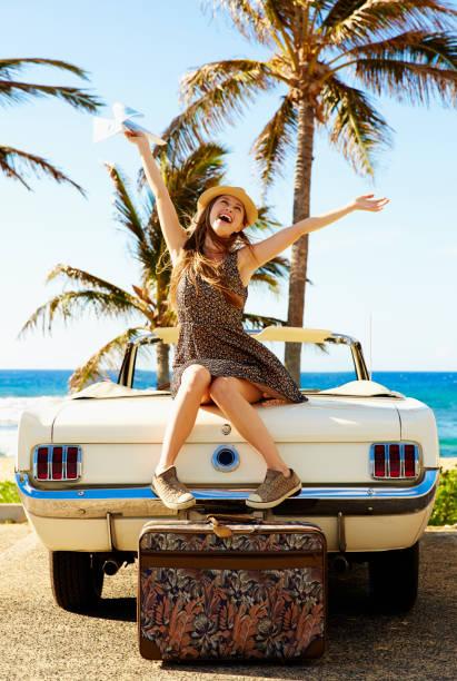 Jeune femme assise sur sa voiture